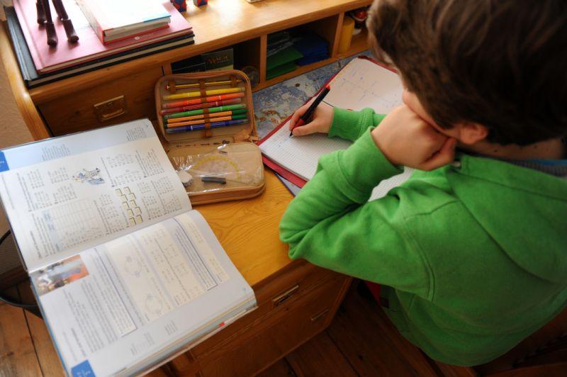 niño haciendo deberes en vacaciones